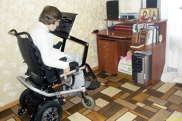 Беспроводная компьютерная клавиатура расположена на инвалидном кресле