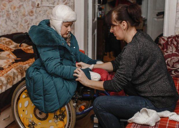 Мама одевает Катю — через пять минут за ними должен приехать волонтер