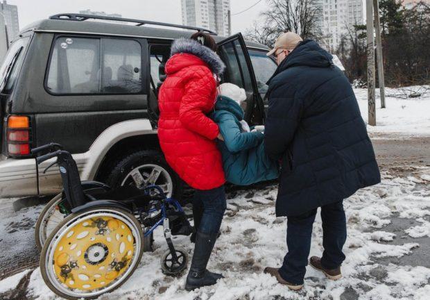 Ирина и Даниил пересаживают Катю из коляски в бустер и пристегивают на заднем сидении