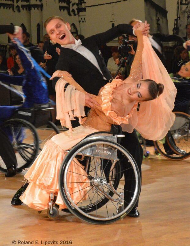 Анна и ее партнер по танцам на соревновании. На Анне надето коралловое бальное платье, на ее партере – фрак