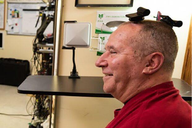 Пациент с двумя беспроводными передатчиками BrainGate на голове